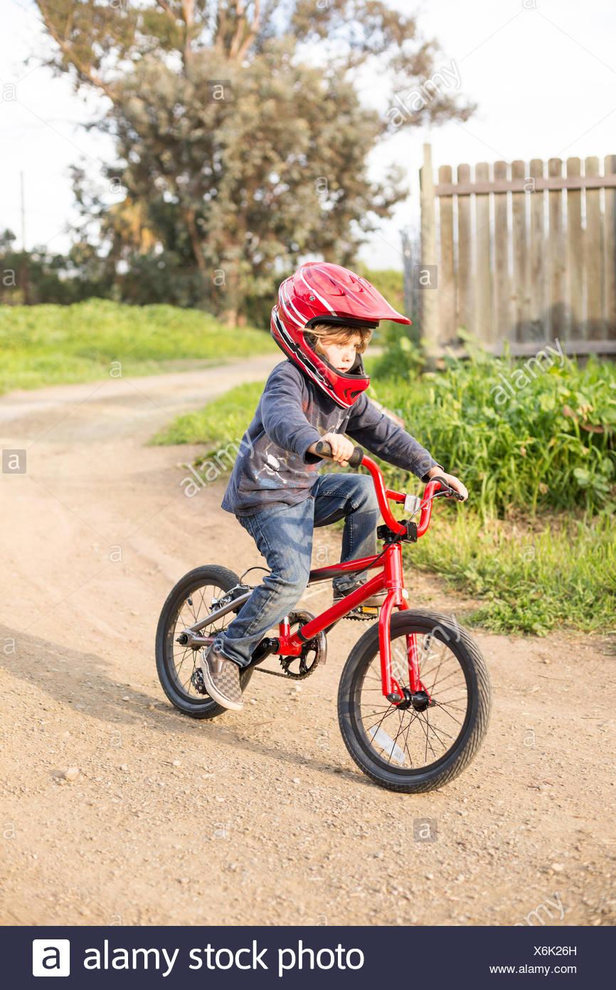 Boy riding a bike on path - Stock Image