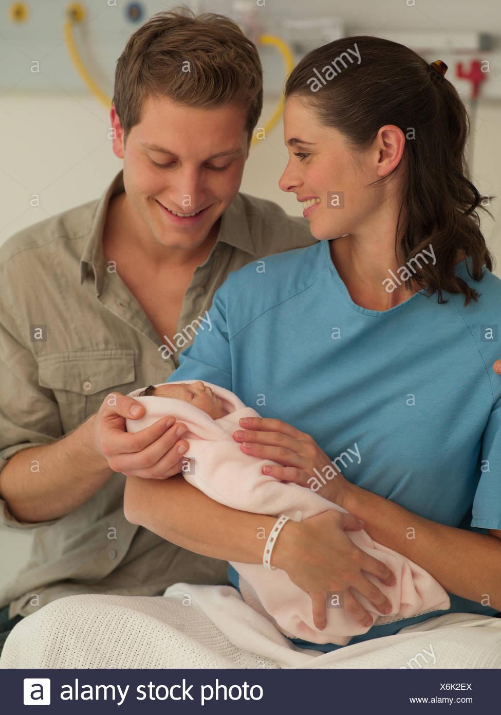 Couple holding newborn baby in hospital - Stock Image