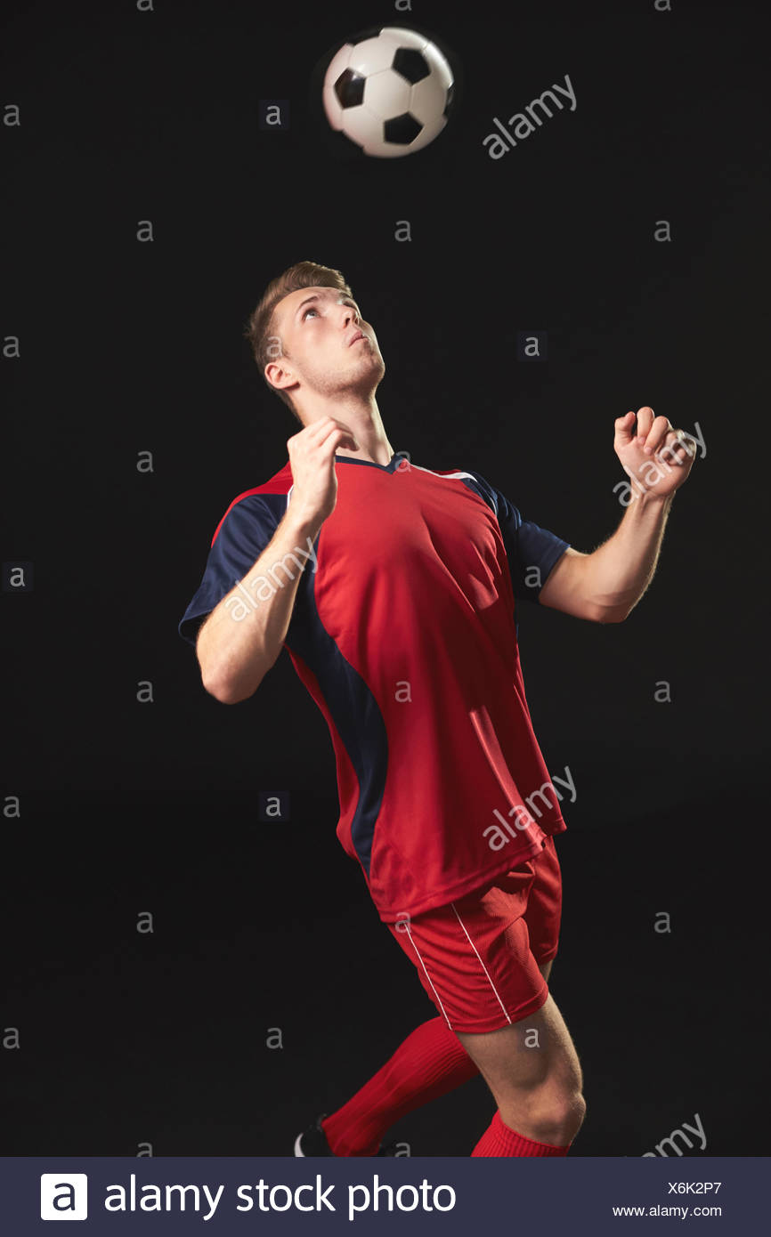 Professional Soccer Player Heading Ball In Studio - Stock Image