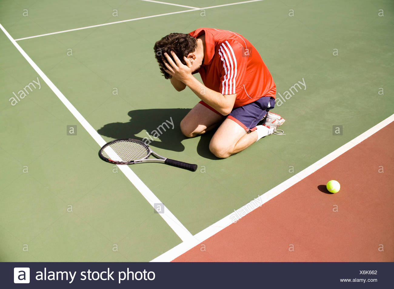 A tennis player kneeling on the court in defeat - Stock Image