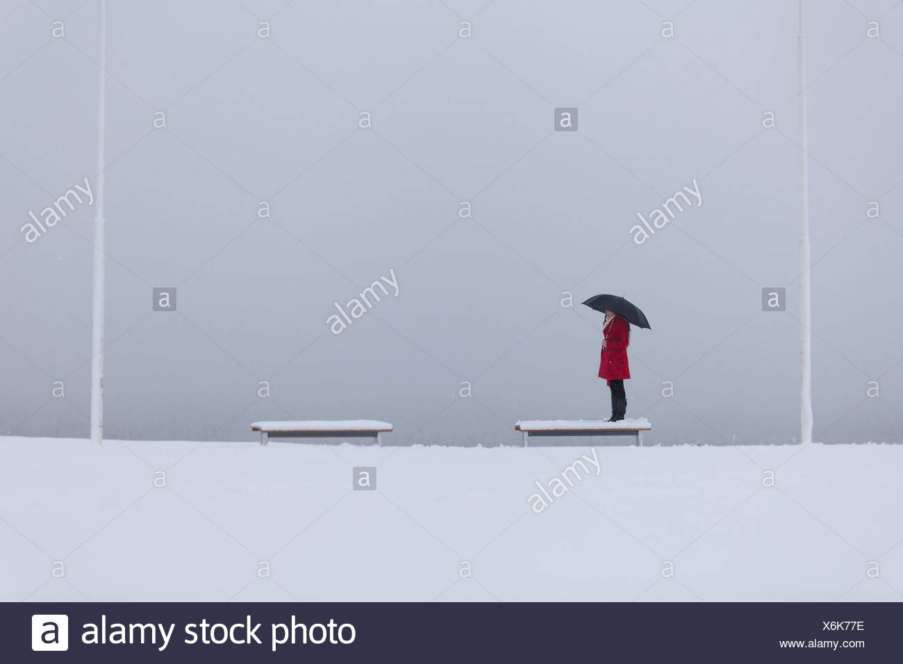 Solitary figure of a young woman wearing a red coat holding an umbrella standing on a bench in the snow - Stock Image
