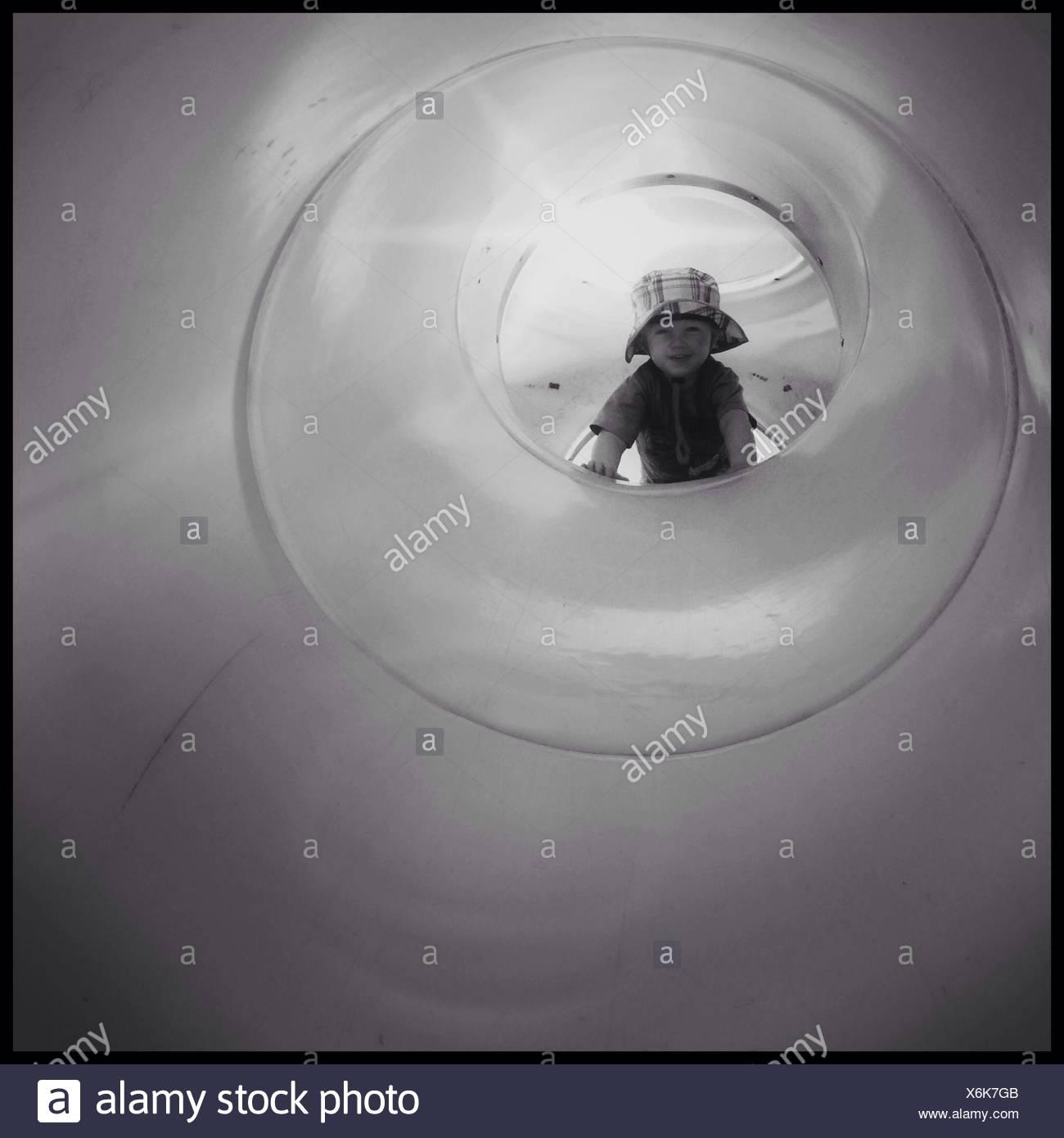 Toddler Looking Through Plastic Slide - Stock Image