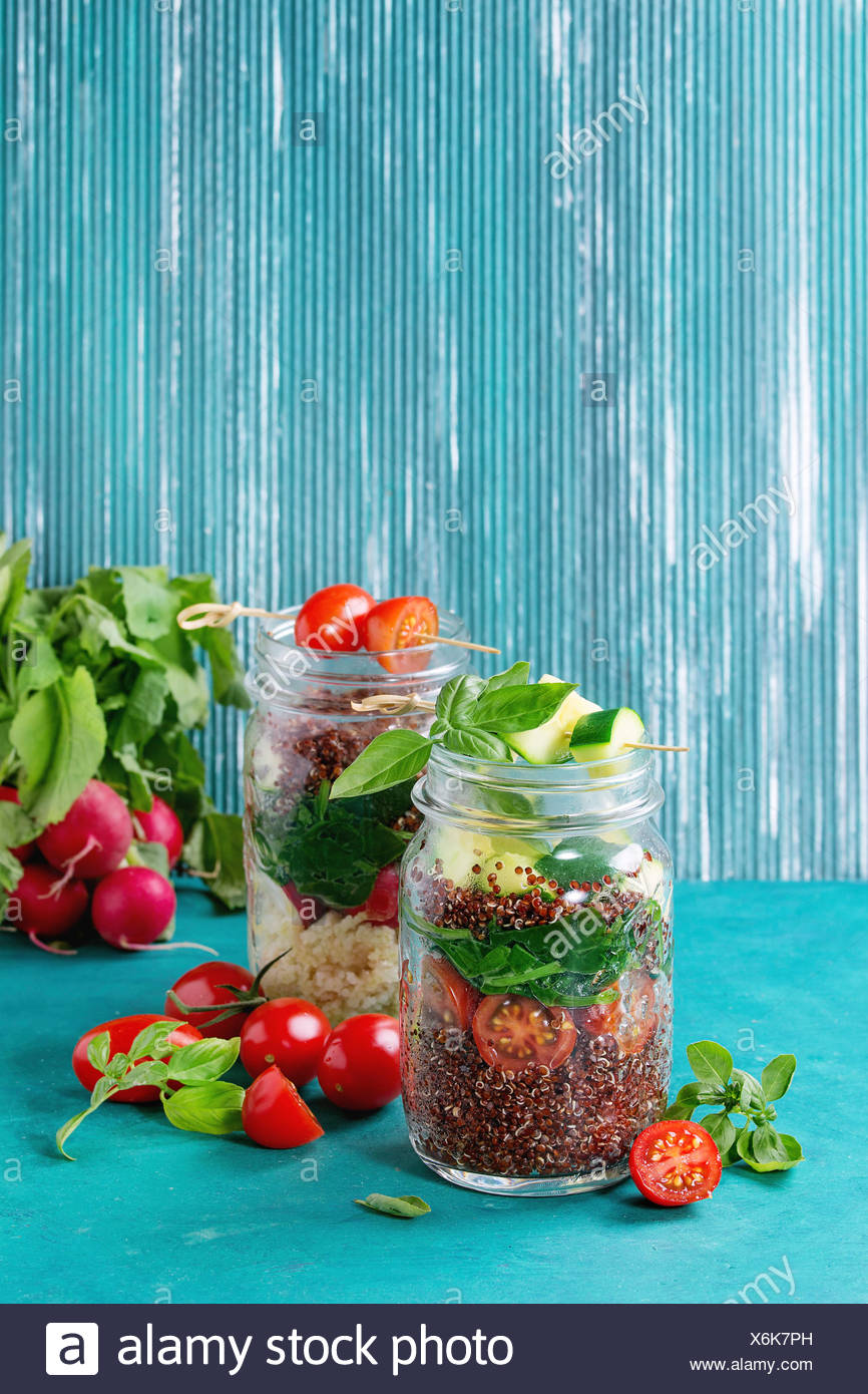 Salads with quinoa, couscous, spinach, radish, tomatoes and zucchini in glass mason jars, standing with fresh vegetables over bright turquoise wooden - Stock Image