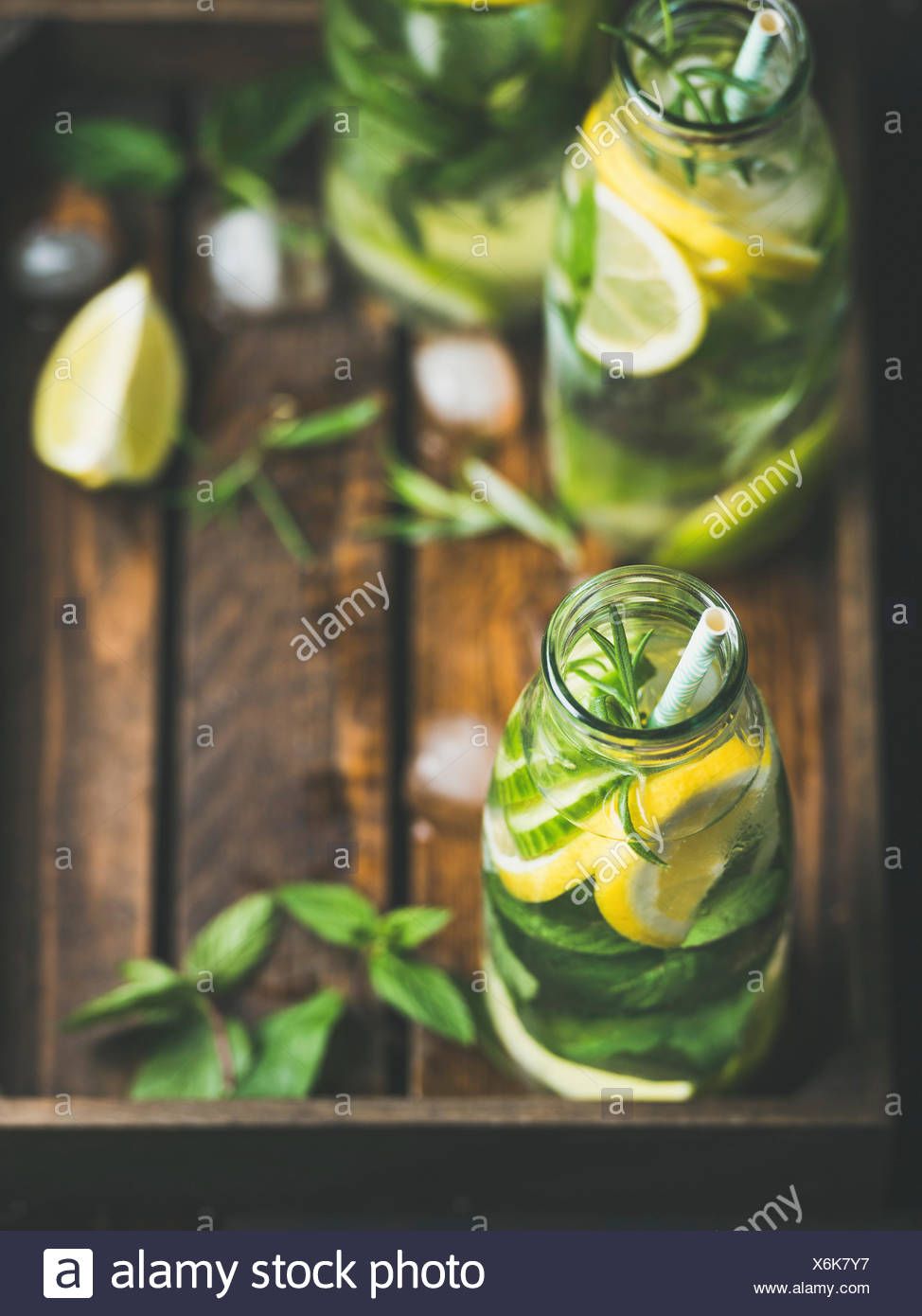 Citrus fruit and herbs infused sassi water for detox, healthy eating, dieting in glass bottles in wooden tray, selective focus, copy space. Clean eati - Stock Image