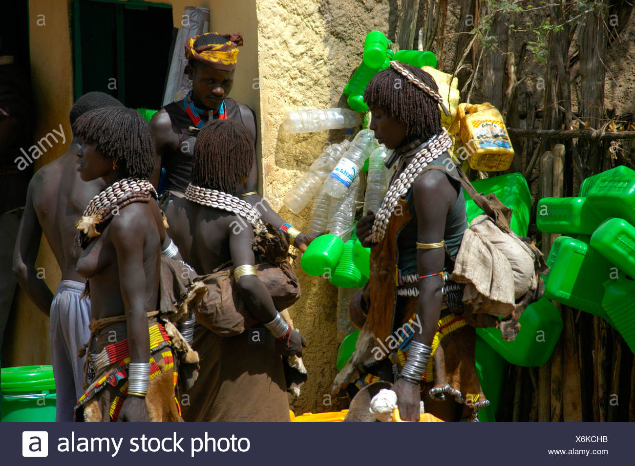 Black skinned Hamar people with white kauri mussel necklaces in front of green plastic canisters, market of Dimeka, Ethiopia, A Stock Photo