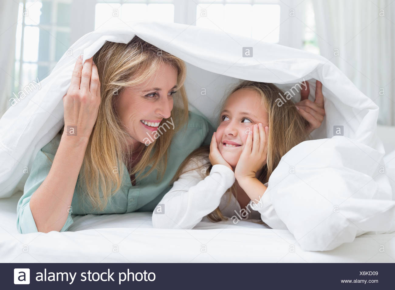 Mother and daughter looking at each other under the duvet - Stock Image