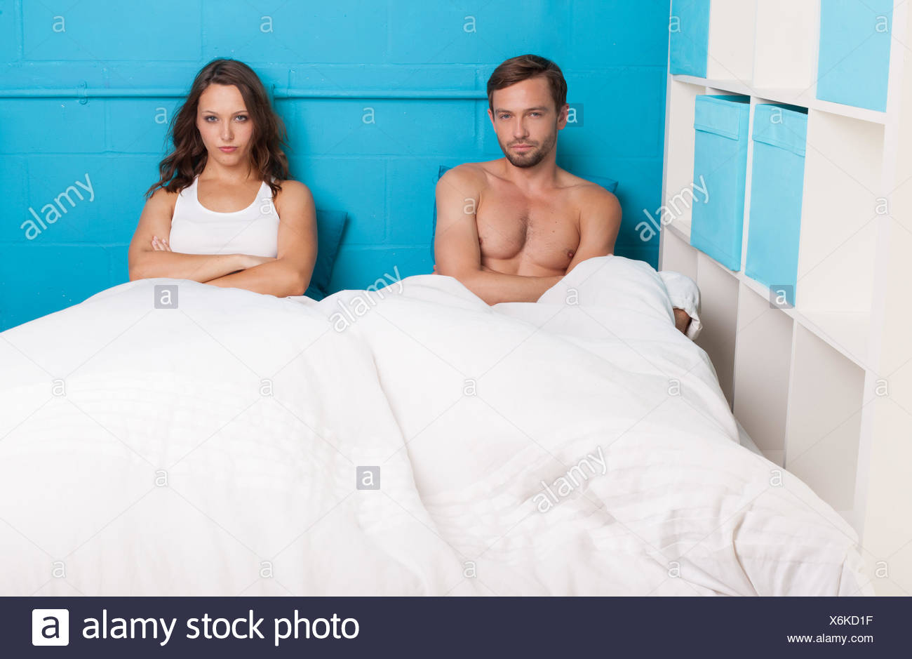 Pessimistic couple having an argument sitting on bed - Stock Image