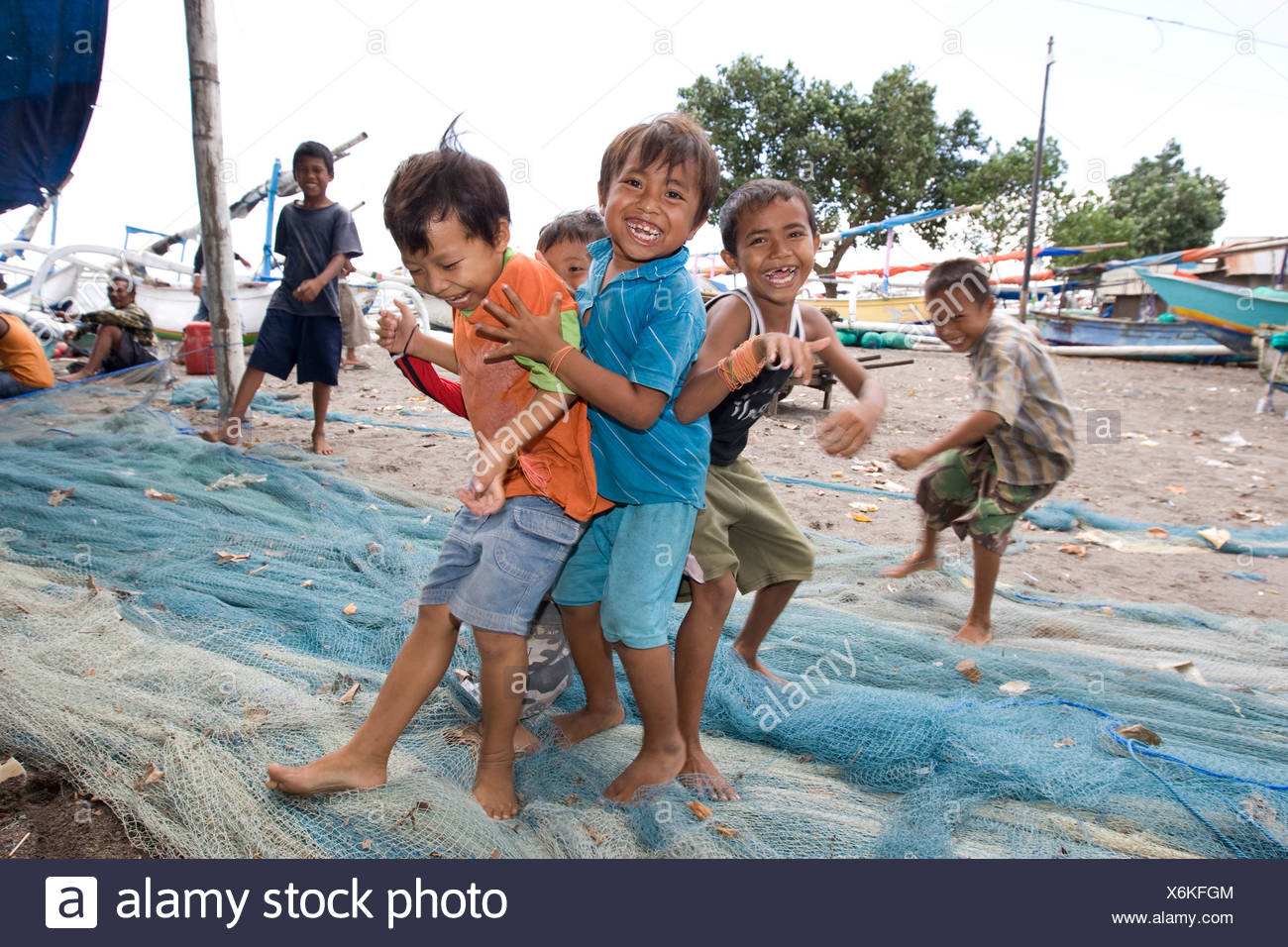Children playing on fishing nets in the harbour, Lombok Island, Lesser Sunda Islands, Indonesia - Stock Image