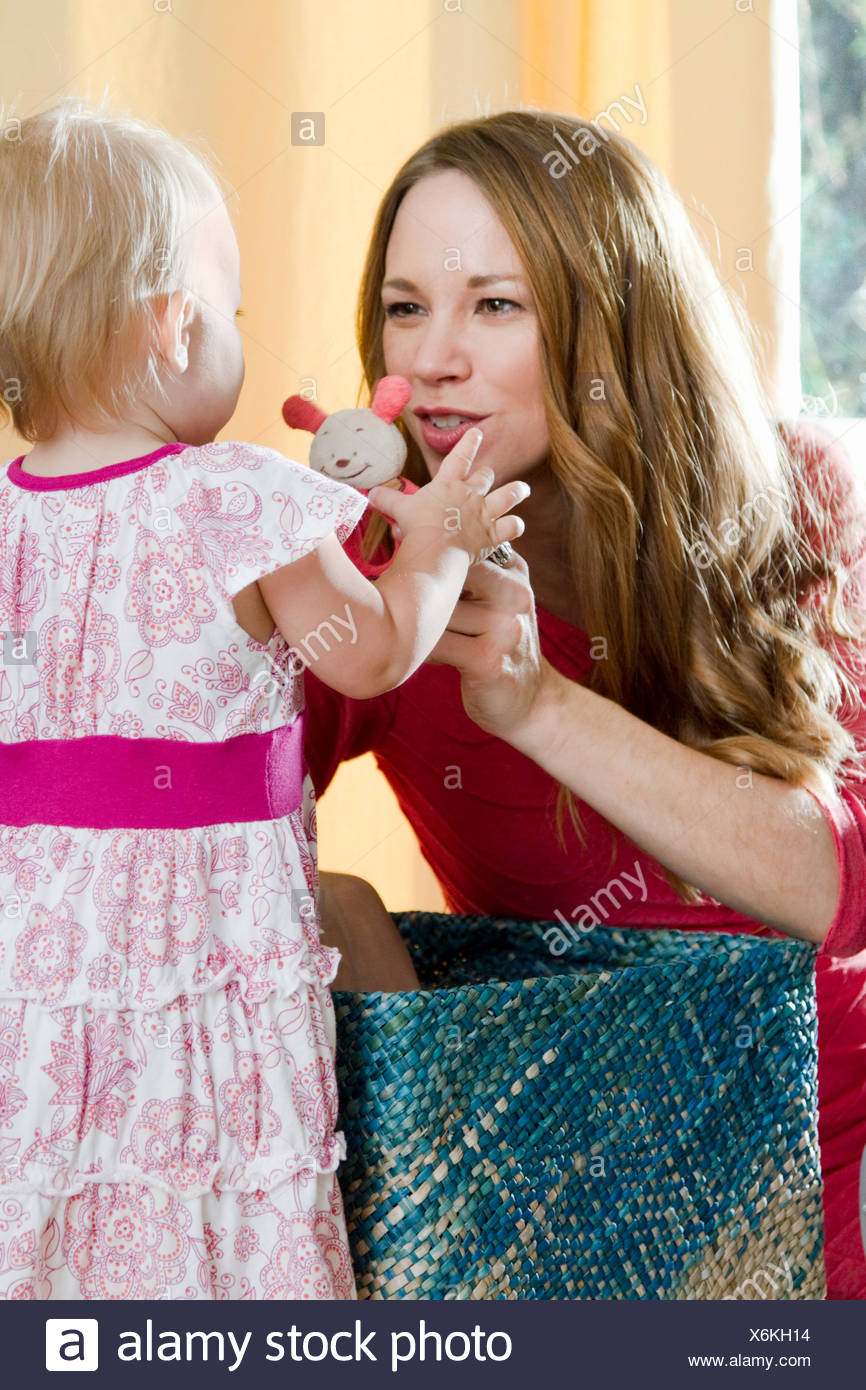 Mid adult mother holding up soft toy for baby daughter - Stock Image