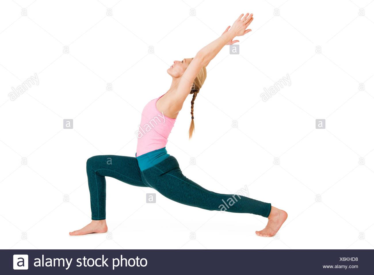 """Seitliche Ganzkörper-Ansicht einer jungen Frau bei Yoga-Übung """"der Krieger 1"""" (Virabhadrasana 1) vor weißen Hintergrund mit leichtem Schatten Stock Photo"""