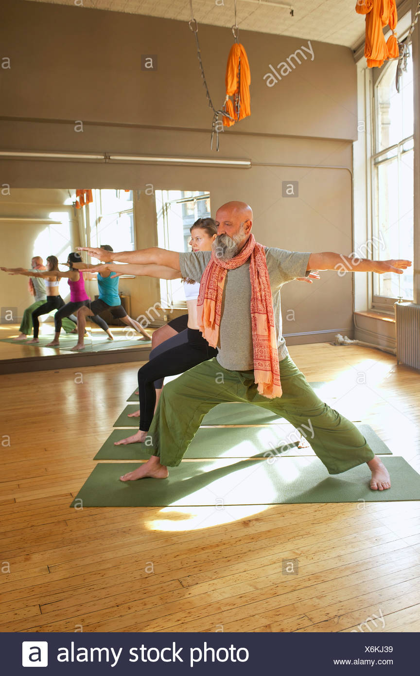 People doing warrior pose in yoga class - Stock Image