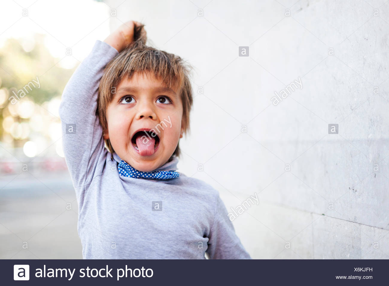 Little boy sticking out tongue while pulling funny face - Stock Image