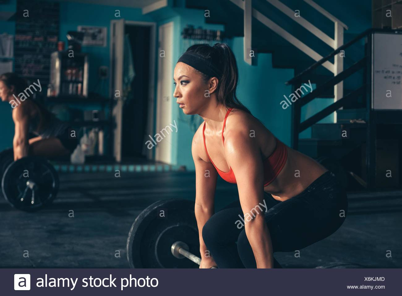 Woman crouching to lift barbell in gym - Stock Image
