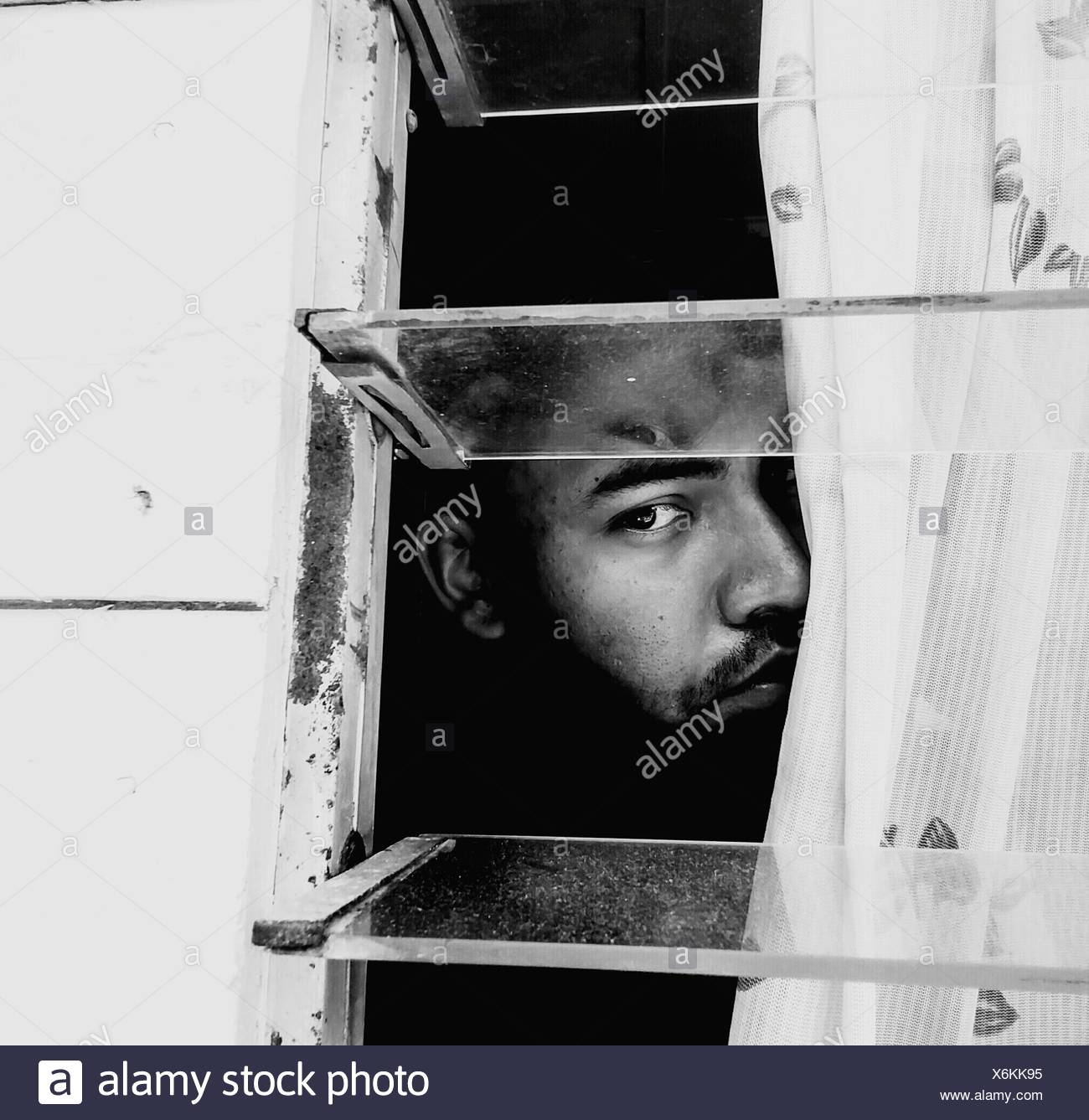 Man Looking Through Window Of House - Stock Image