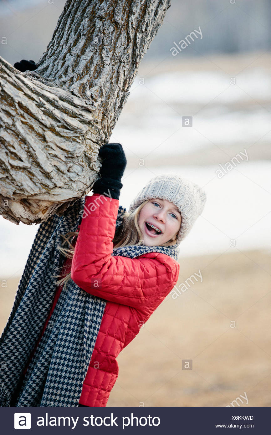 A young girl in a red jacket, and long scarf, gripping a tree trunk. - Stock Image
