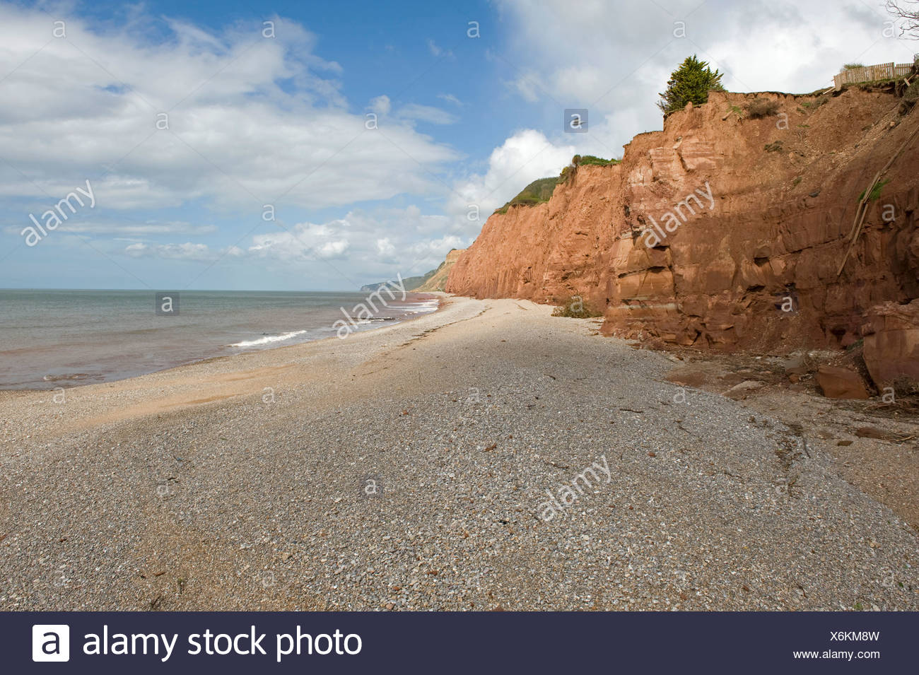 Crumbling red sandstone East Cliffs at Sidmouth which are being severely eroded by the sea - Stock Image