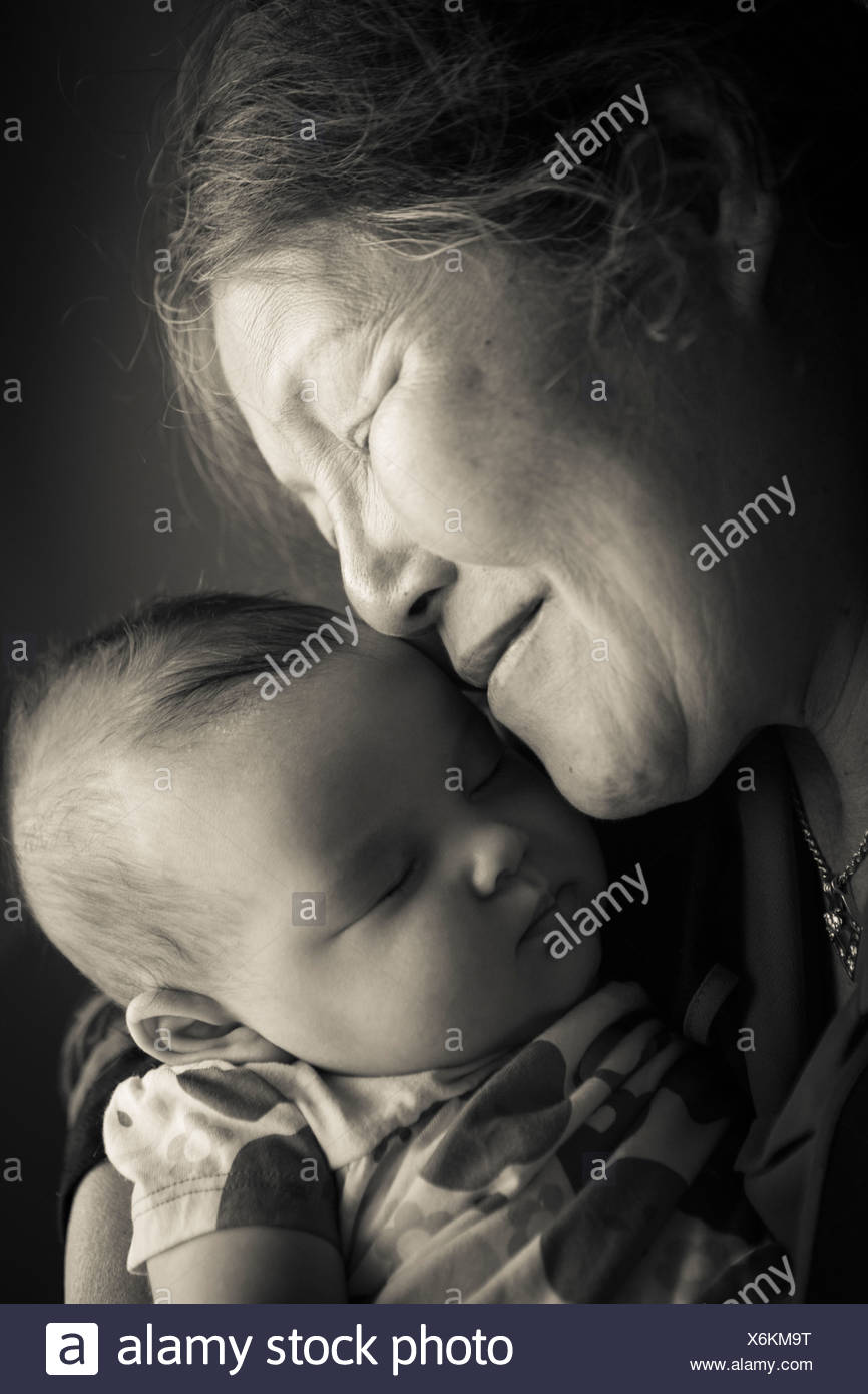 Portrait of grandmother holding baby granddaughter - Stock Image