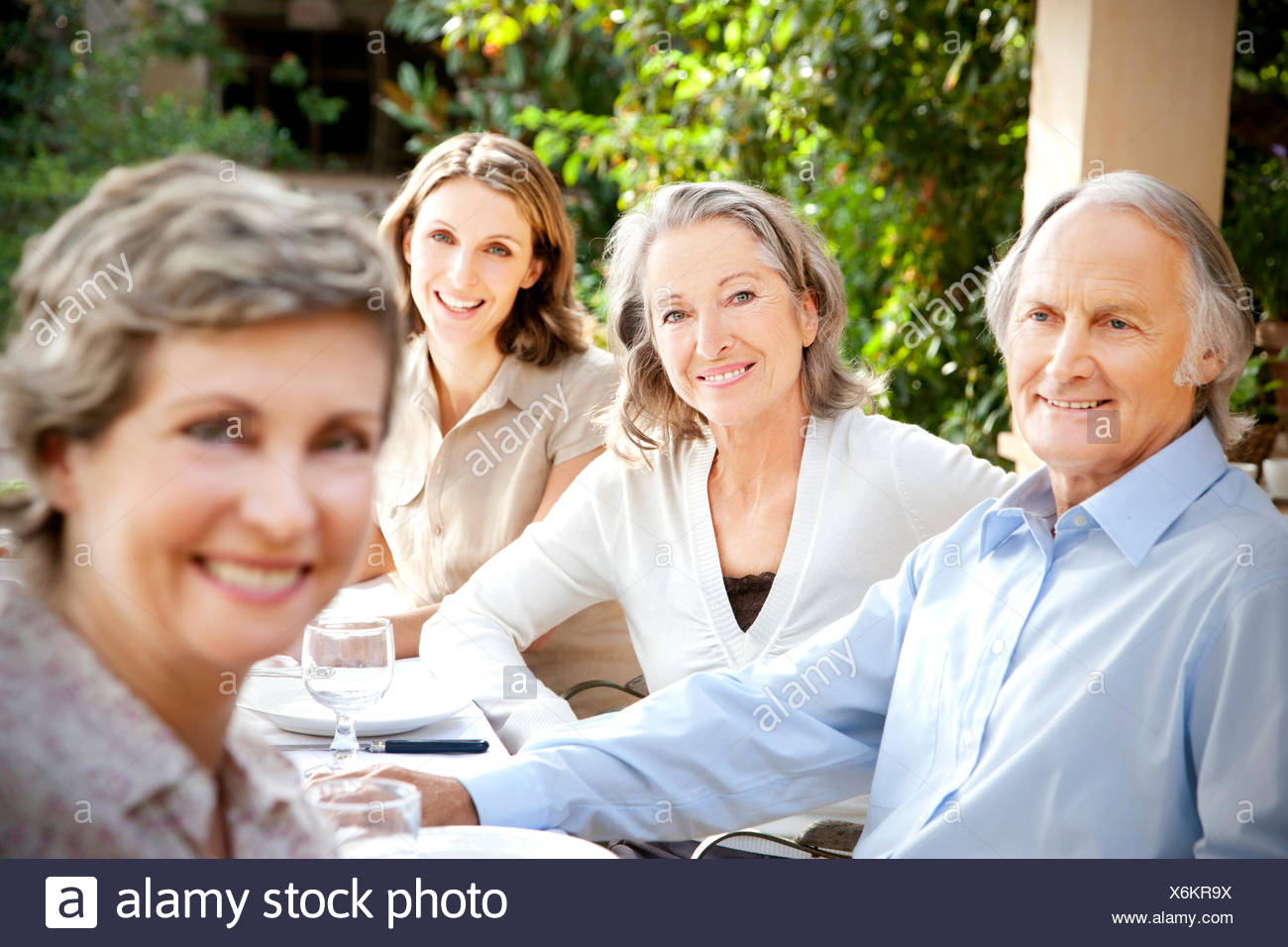 Four smiling friends sitting at laid table in the garden - Stock Image