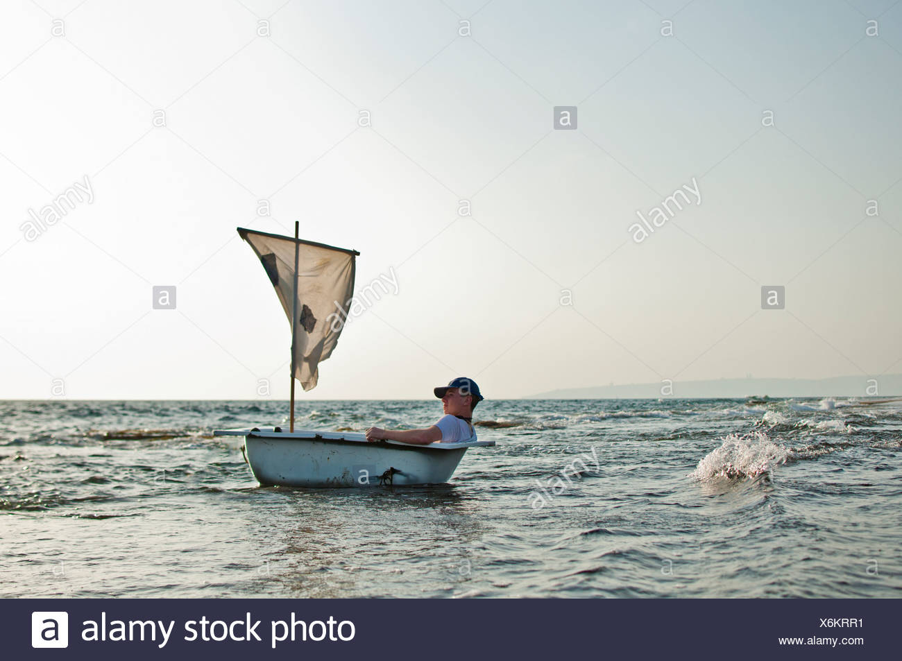 Man in a bathtub like boat with a sail in the sea - Stock Image