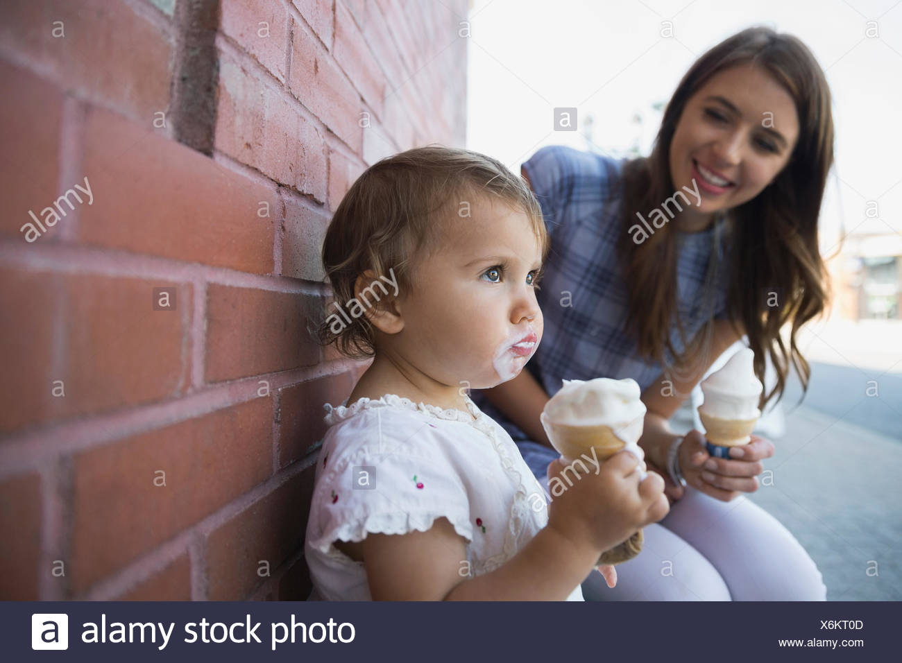 Mother and daughter eating soft serve ice cream - Stock Image