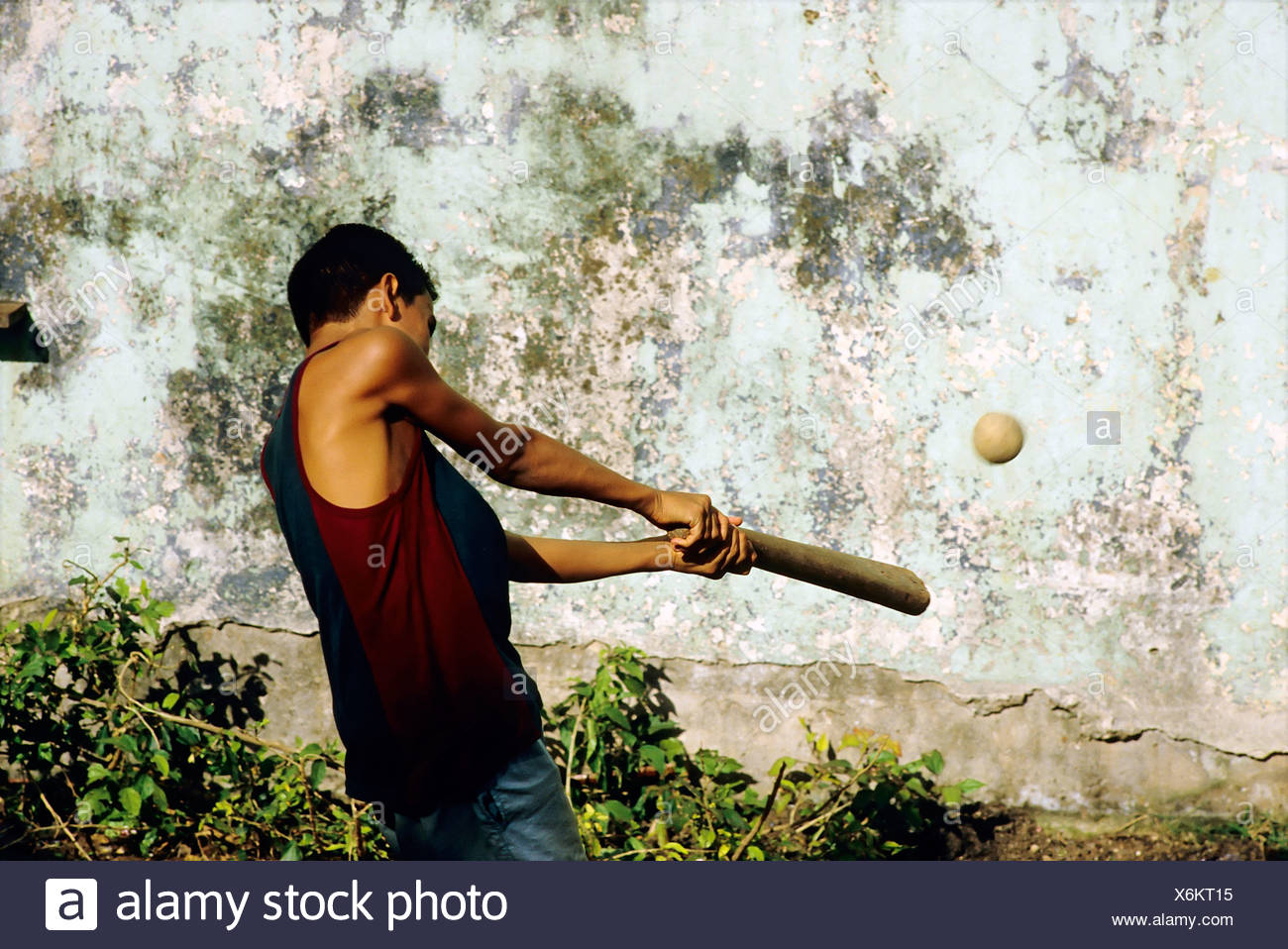 Boy hitting a ball with a baseball bat in front of a weathered house wall, Centro Habana, Havana, Cuba, Caribbean - Stock Image
