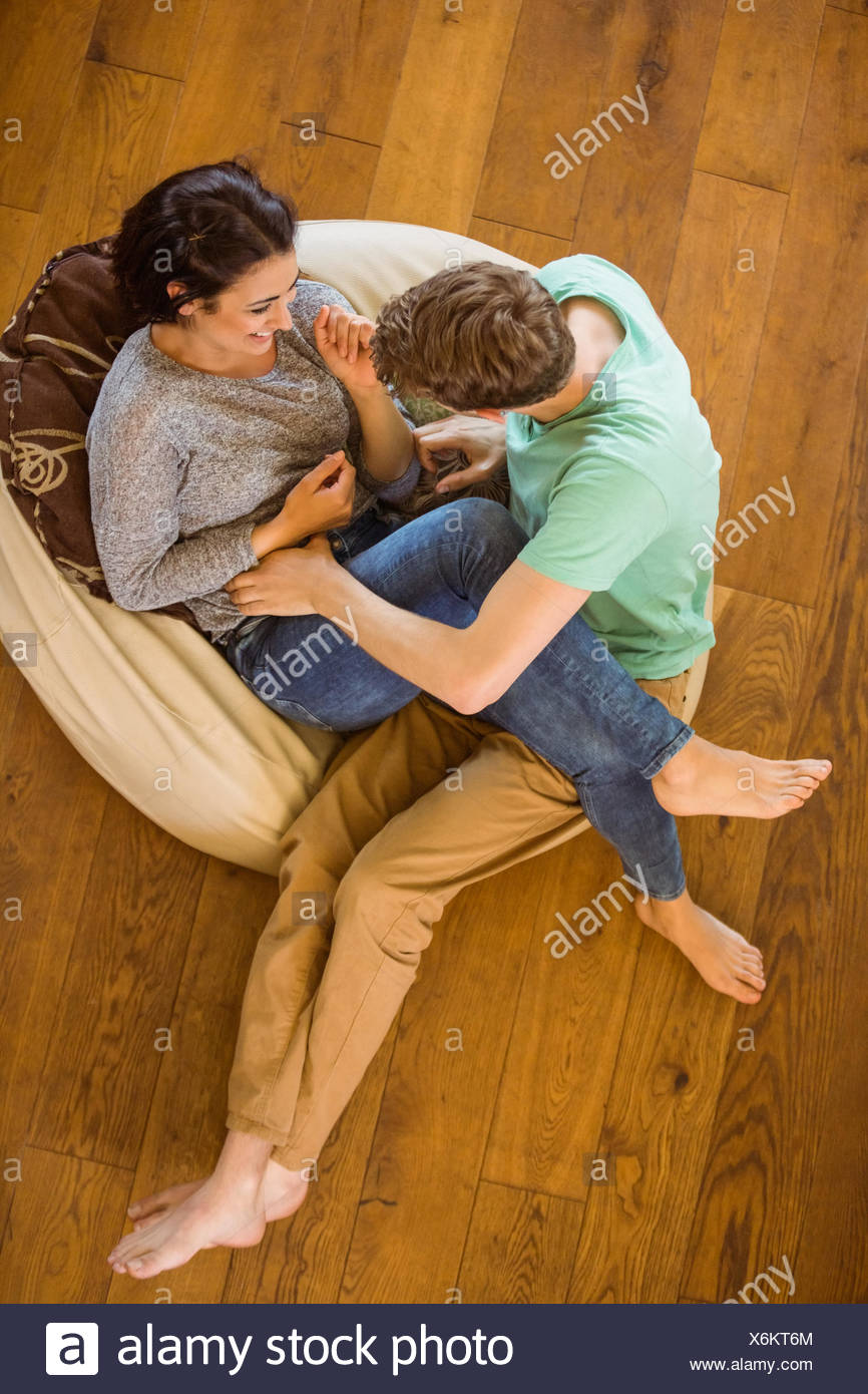 Cute couple laughing together on beanbag - Stock Image