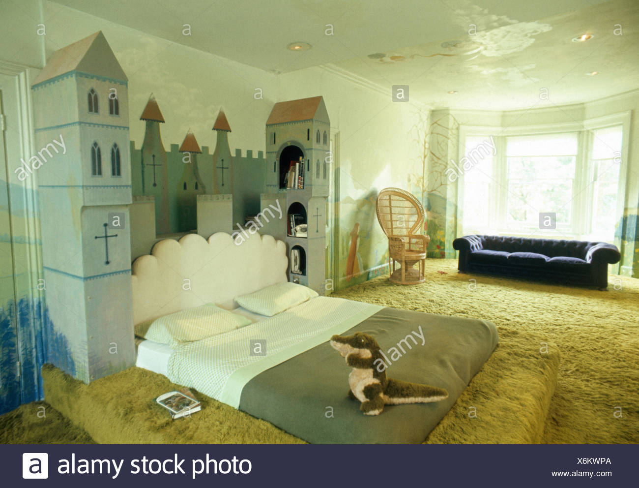 Castle themed bed in child's seventies bedroom with shag pile carpet - Stock Image