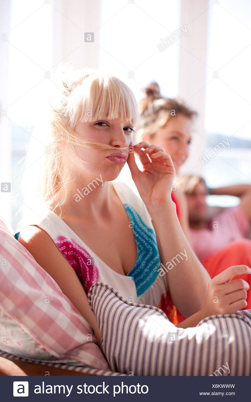 Woman making face and holding hair above lip - Stock Image