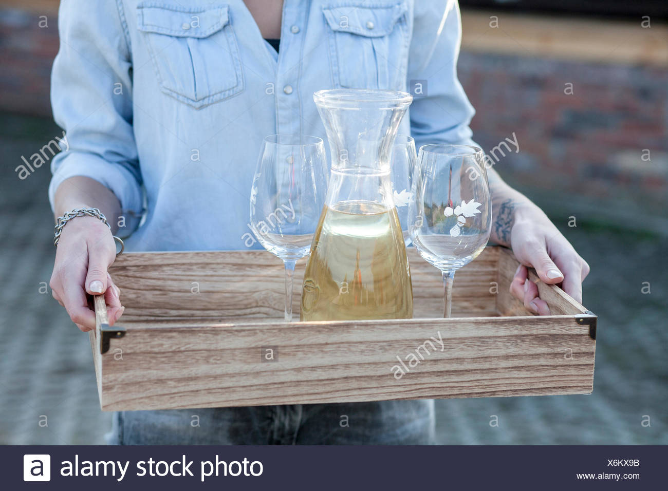 Woman serving white wine on tray - Stock Image