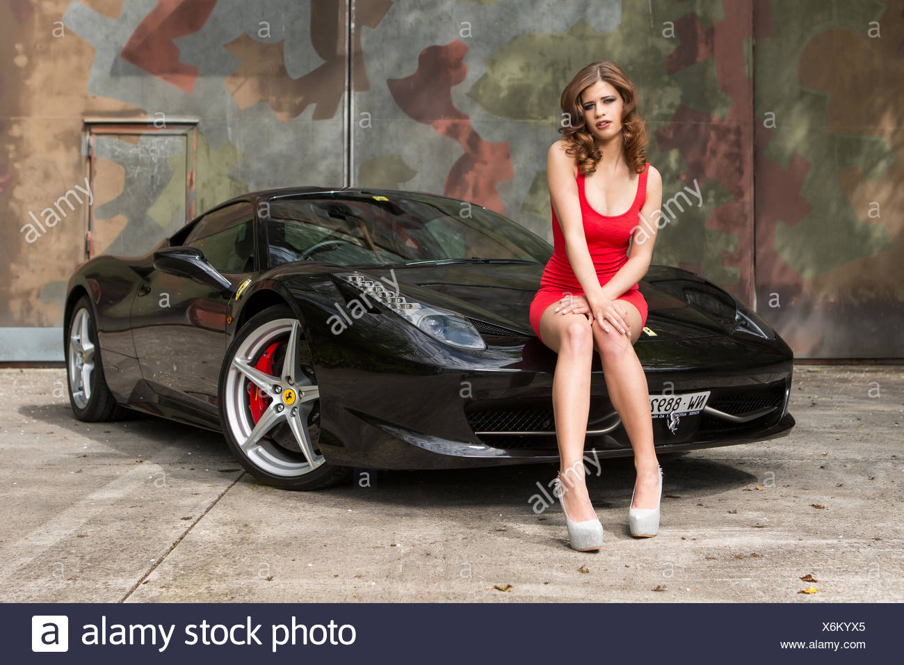 Young Woman Wearing A Red Dress Posing On A Black Ferrari 458 Italia Stock Photo Alamy