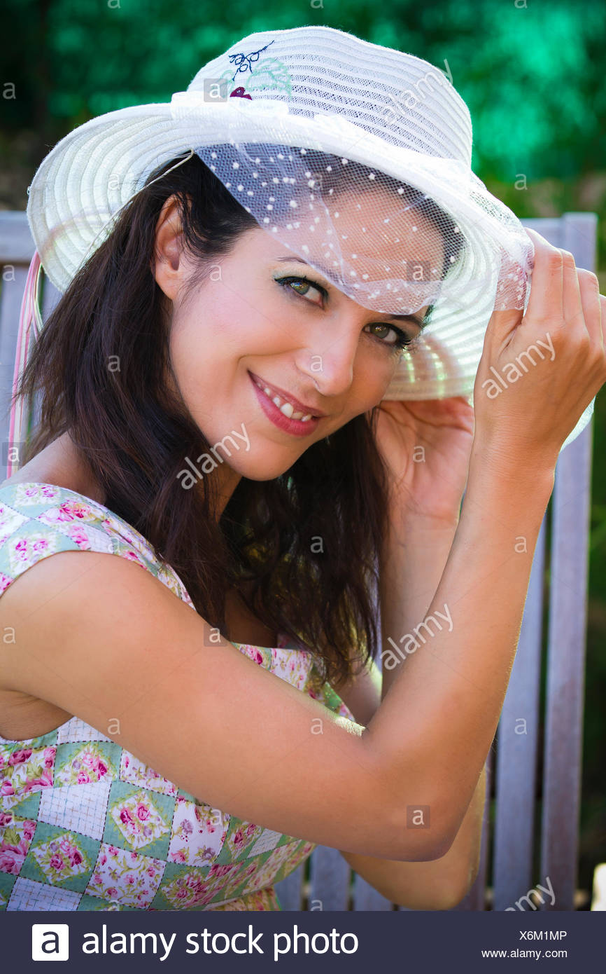 59cd0882 beautiful young brunette in a summer garden with white hat Stock ...