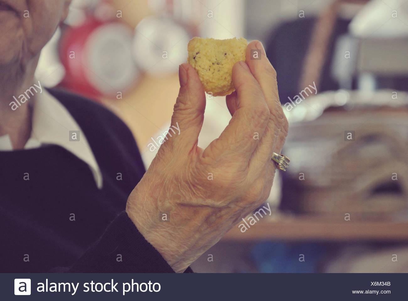 Elderly lady eating cake - Stock Image