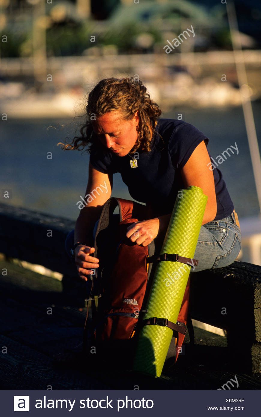 Woman sitting on warf at public market. Granville Island, Vancouver, British Columbia. - Stock Image