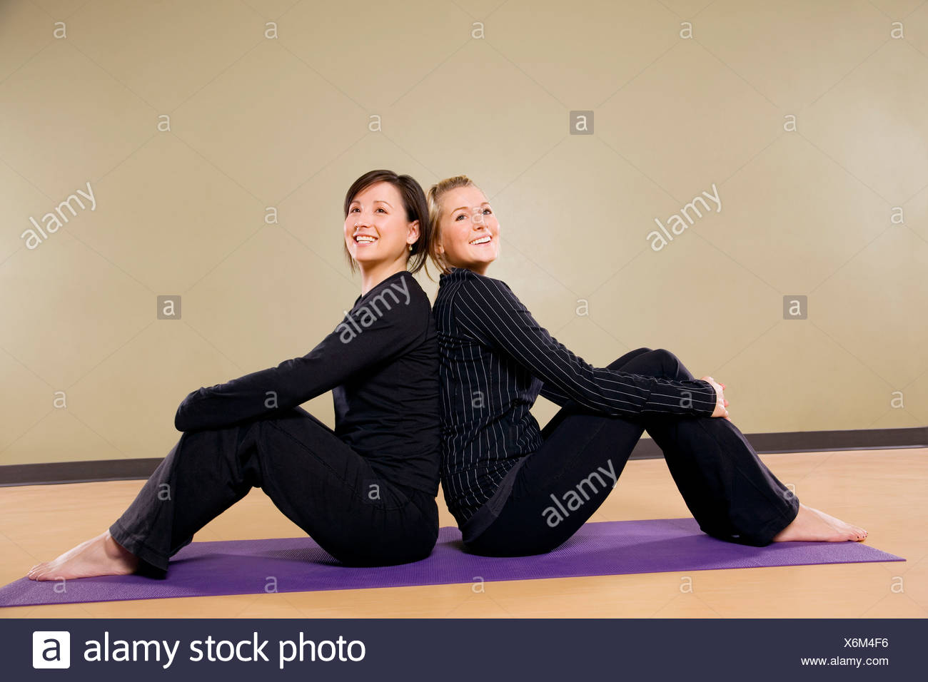 Two women sitting back to back - Stock Image