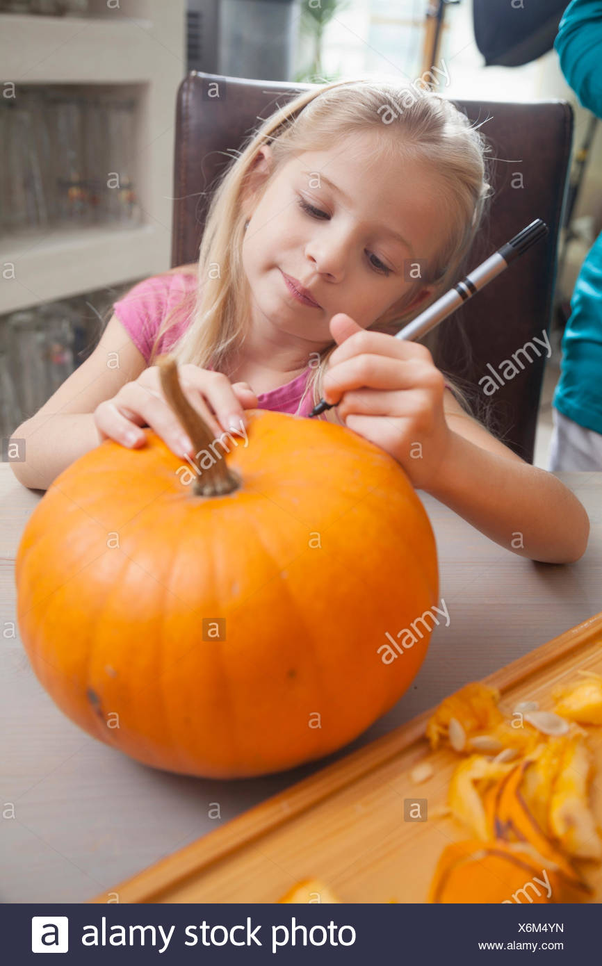 Girl carving pumpkin for Halloween, Bavaria, Germany - Stock Image