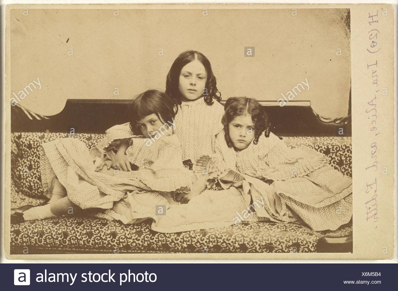 Edith, Ina and Alice Liddell on a Sofa. Artist: Lewis Carroll (British, Daresbury, Cheshire 1832-1898 Guildford); Person in Photograph: Person in - Stock Image
