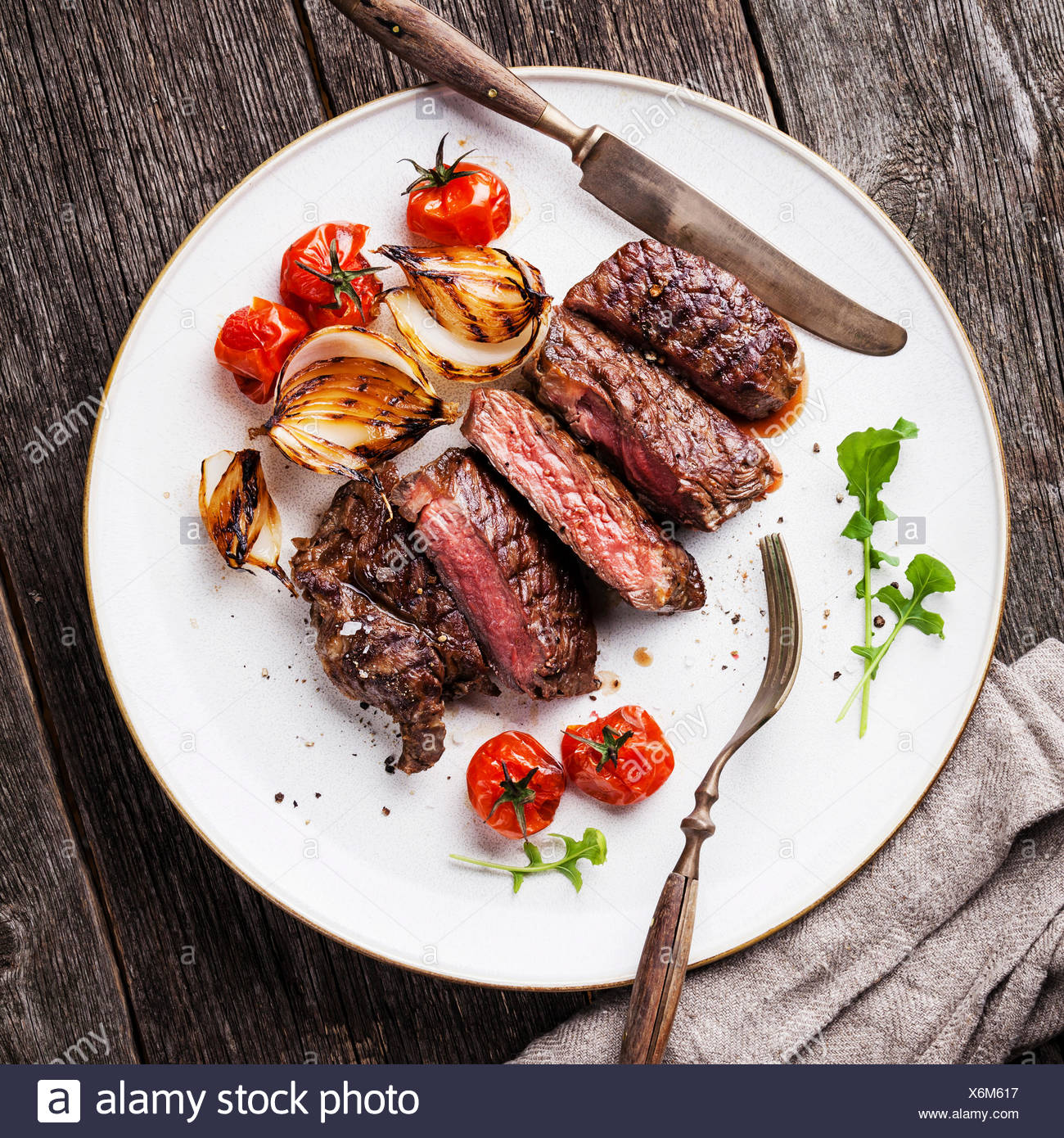 Sliced Medium Rare Grilled Beef Steak Ribeye With Grilled Onions And Cherry Tomatoes On Plate On Wooden Background Stock Photo Alamy