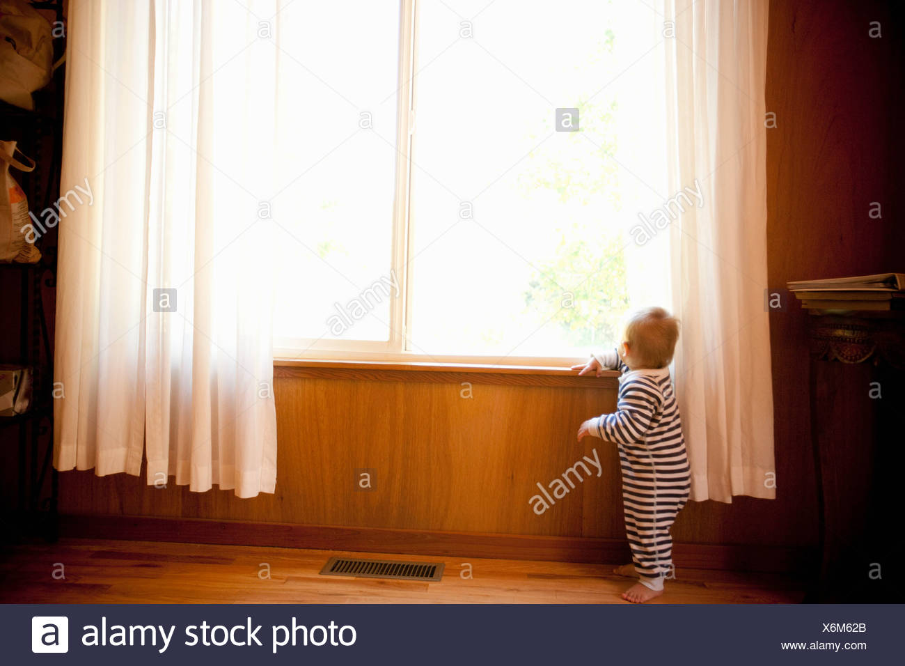Toddler boy looking out of window - Stock Image
