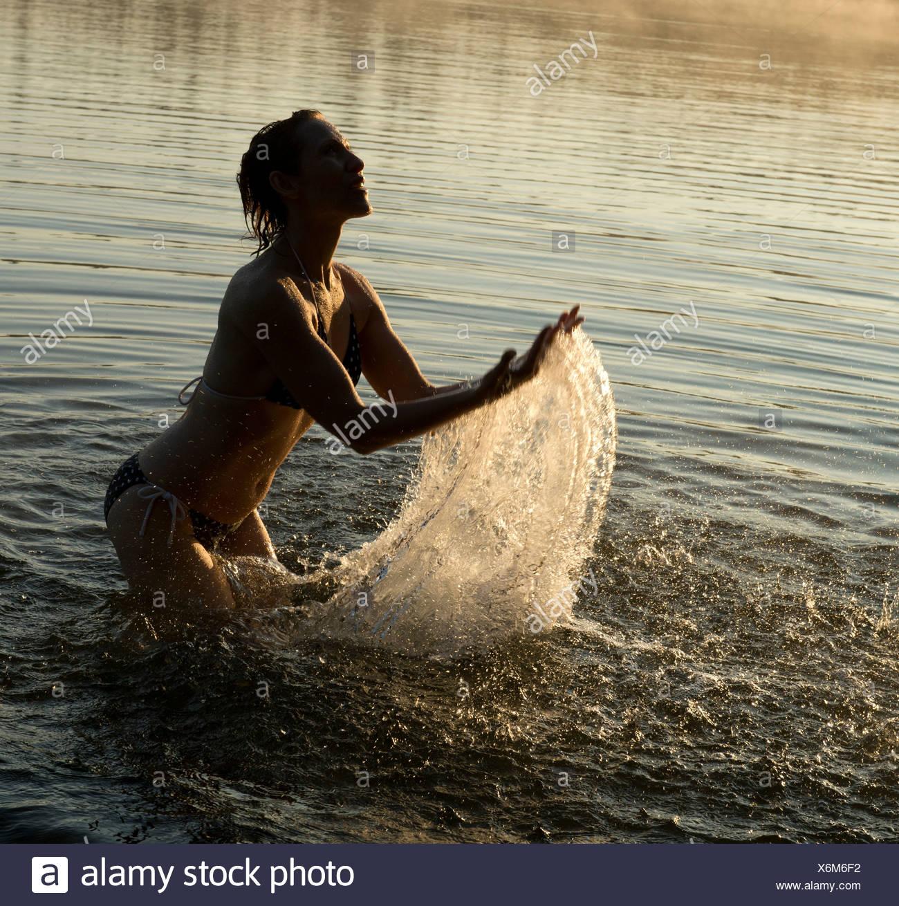 Woman splashing in water of lake - Stock Image