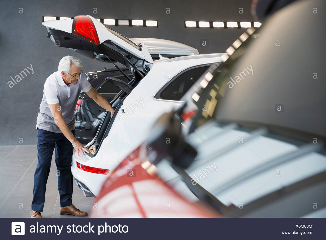 Man looking inside car in car dealership showroom Stock Photo