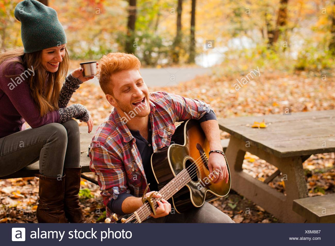 Young couple playing guitar on picnic bench in autumn forest - Stock Image