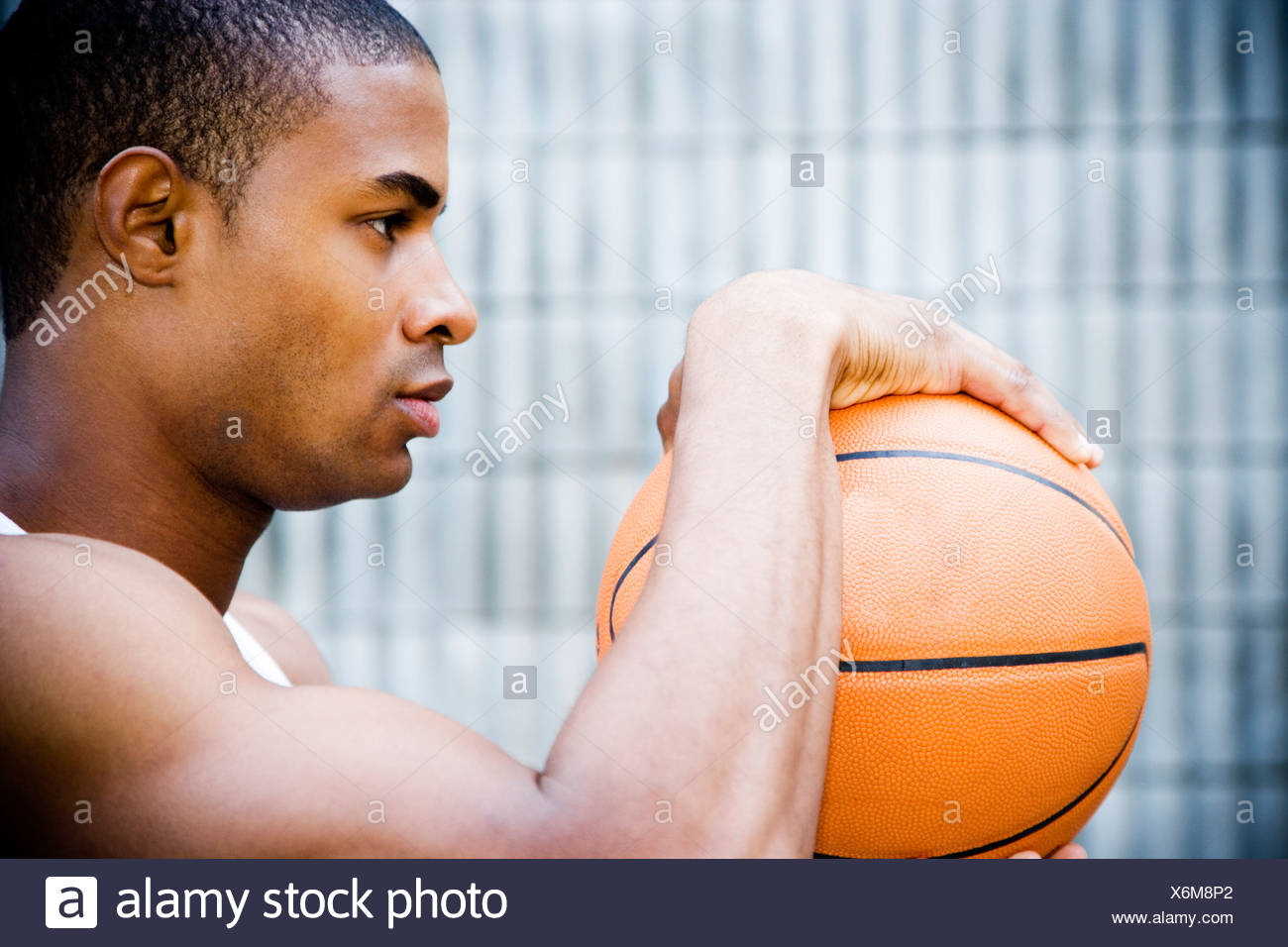 Portrait of a young African American man holding a basketball. - Stock Image