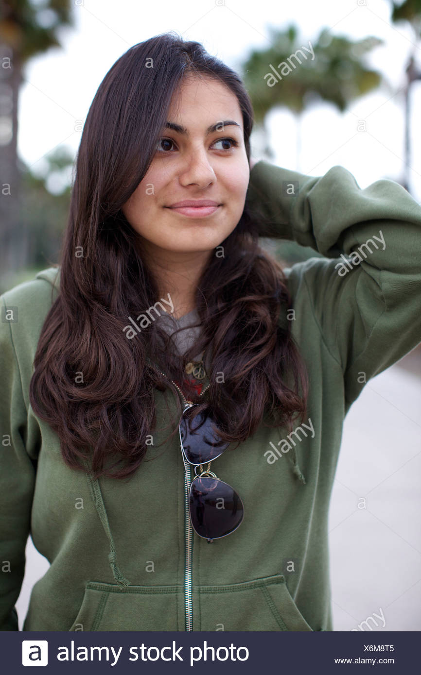 Young lady with dark hair and dark eyes smiles and touches her hair at the park. - Stock Image