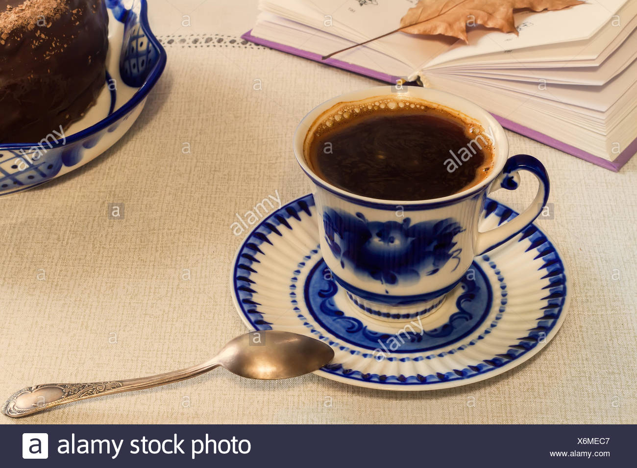 A Cup of black coffee and cake on the table. - Stock Image
