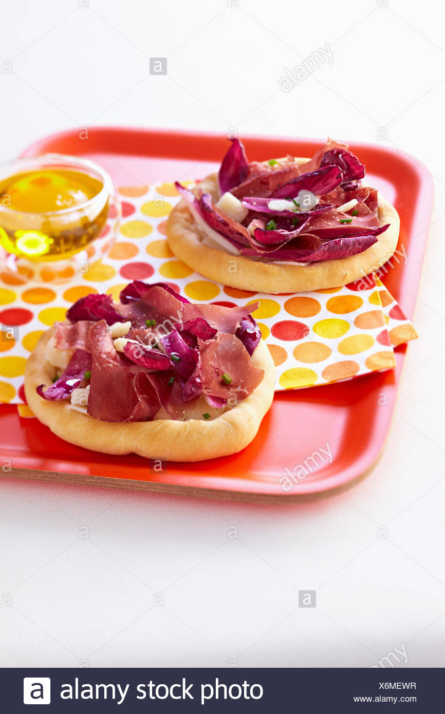 Chicory,grisons meat and parmesan flake mini pizzas - Stock Image
