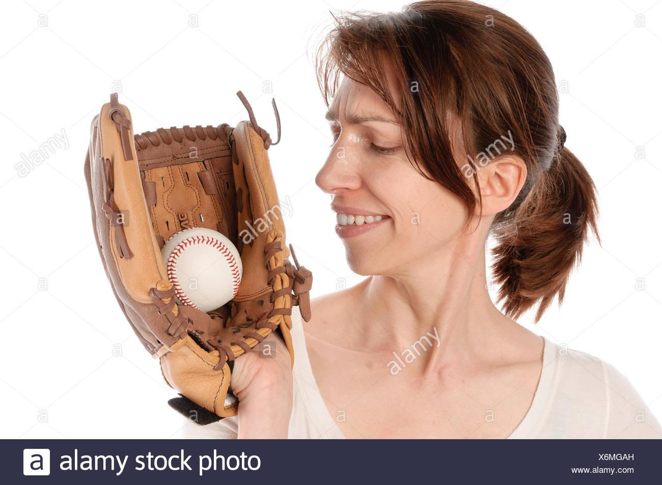 Erwachsene Frau mit Baseballhandschuh und weißer Sportkleidung vor weißem Hintergrund - Stock Image