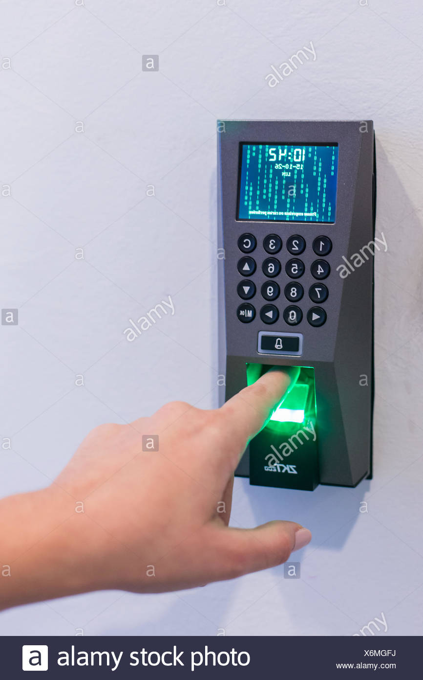 Nurse's finger being scanned by a fingerprint scanner. - Stock Image