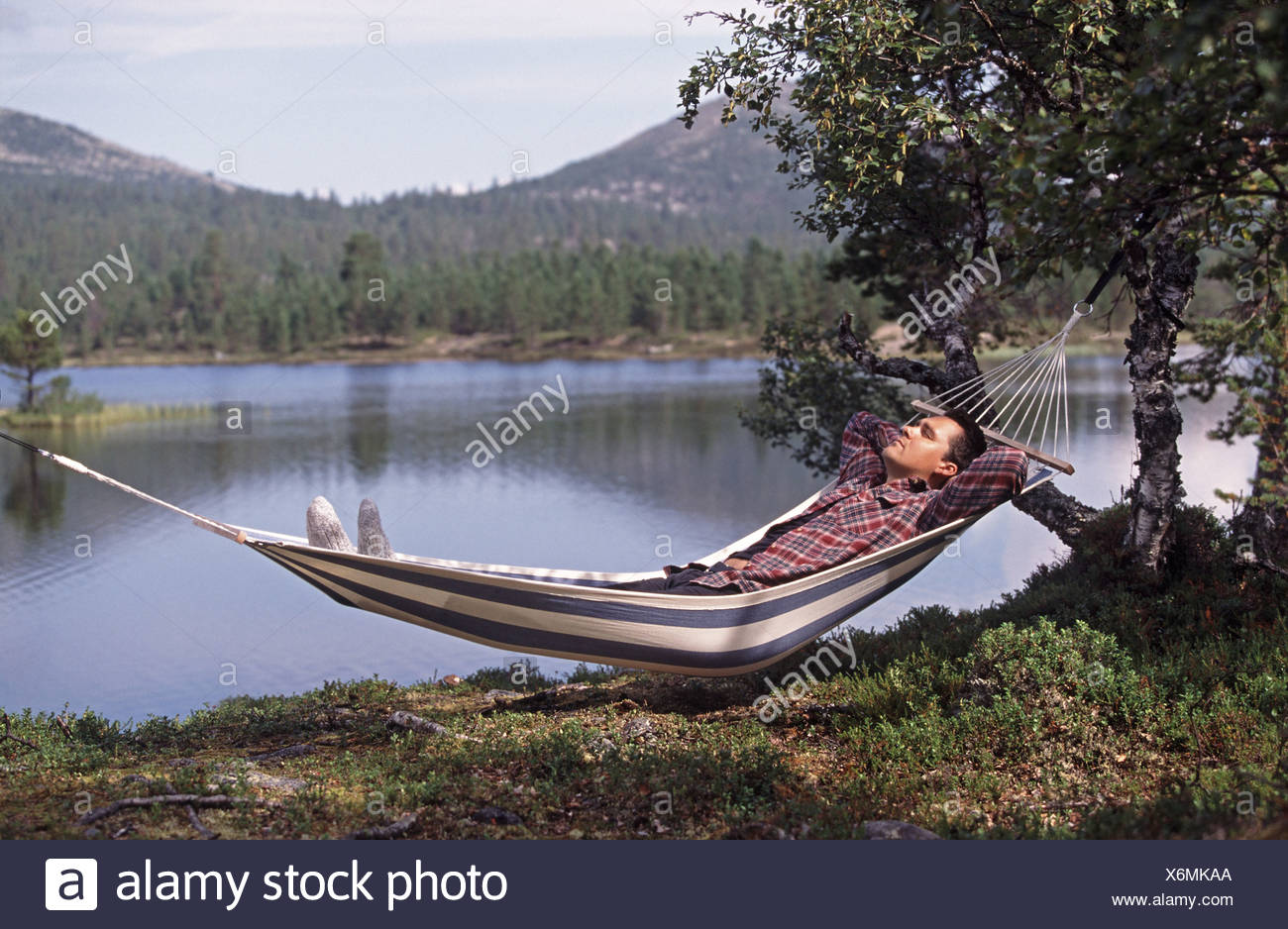 Man laying in a hammock and in background mountains and a lake - Stock Image