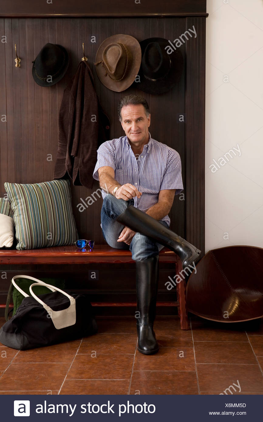 Man wearing riding boots indoors Stock