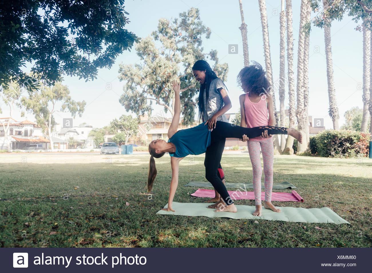 Girls and teenage schoolgirls practicing yoga standing half moon pose on school playing field - Stock Image